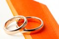 Gold wedding rings near orange ribbon with space for text Stock Images