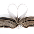 Gold wedding rings old book and paper heart on a white background Royalty Free Stock Photography