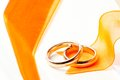 Gold wedding rings orange ribbon near on white background Stock Image