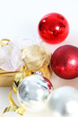 Gold wrapped gift with christmas baubles shiny red and silver and a decorative bow in a seasonal background Stock Photography