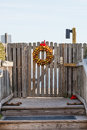 A gold wreath at christmas hanging on a gate in walkway toward beach Stock Image