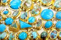 Golded jewel with turquoise fashion jewelry from yellow gold on a window shop Royalty Free Stock Photography