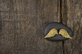 Golden angel wings with black stone on old wooden background for Royalty Free Stock Photo