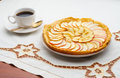 Golden apple tart and coffee cup a tasty homemade a of black on an embroidered tablecloth Stock Photography