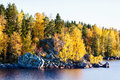 Golden autumn forest and large rocks by a lake in sunshine Stock Image