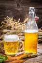 Golden beer made ​​of wheat and hops on old wooden table Stock Photos