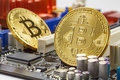 Golden bitcoins on the computer motherboard background closeup. Cryptocurrency virtual money Royalty Free Stock Photo