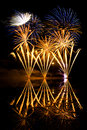 Golden and blue fireworks reflected in a murky lake Royalty Free Stock Photo