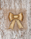 Golden bow on the burlap textile and old wood background Stock Photo