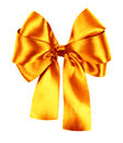 Golden bow made from silk ribbon on white Stock Photos