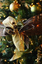 Golden bows on christmas tree hanging a with ornaments to celebrate the holidays Stock Image