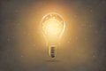 Golden brain glowing inside light bulb on paper texture Royalty Free Stock Photo