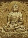 Golden Buddha, an ancient sculpture bas-relief on the wall, Tibet.