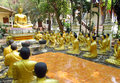 Golden Buddha and monks statues in Buddhist temple