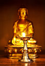 Golden Buddha with oil lamp Stock Photography