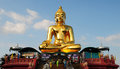 Golden buddha statue on asian temple building with blue sky and cloudscape background Stock Photos