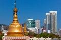 Golden buddhist stupa on modern city buildings background Royalty Free Stock Photo