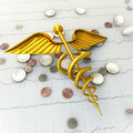Golden Caduceus on Ecg - Ekg Paper with Coins - Spending Money  Stock Images
