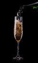 Golden champagne in glass pouring from a bottle Royalty Free Stock Photography