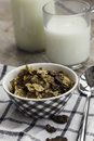 Golden and chocolate cornflakes in a bowl and a glass of milk on the wooden table