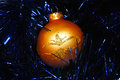 Golden christmas ball on blue tinsel background Royalty Free Stock Images