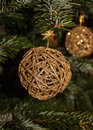 Golden Christmas braided ball on Christmas tree background. Stock Photos