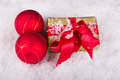 Golden christmas gift with red christmas balls in the snow for Stock Photo
