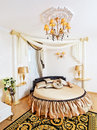 Golden classical bedroom interior with round bed Royalty Free Stock Photo