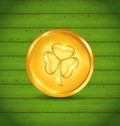 Golden coin with clover on green wooden texture for St. Patrick