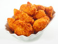 Golden crisp fried chicken nuggets crumbed served in a fluted dish as an appetizer or finger food on a white background Stock Photos