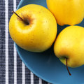 Golden delicious apples yellow in blue plate on striped tablecloth top view point Stock Photography