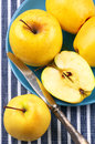 Golden delicious apples yellow in blue plate with vintage knife on striped tablecloth top view point Royalty Free Stock Images