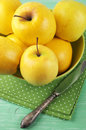 Golden delicious apples yellow in green bowl with napkin on rustic wooden table Royalty Free Stock Images