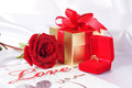 Golden diamond ring with gift box and red rose on with satin background Stock Image