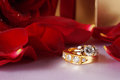 Golden diamond ring with gift box and red rose on with satin background Stock Photo