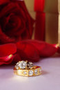 Golden diamond ring with gift box and red rose on with satin background Royalty Free Stock Photography