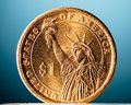 Golden dollar coin on blue background Royalty Free Stock Photo
