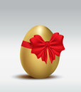 Golden Easter egg with red ribbon Royalty Free Stock Image