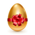 Golden egg with red bow Royalty Free Stock Photos