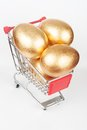 Golden eggs three on the shopping cart Stock Photos