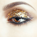 Golden eye makeup close up shot of female face with vogue shining Royalty Free Stock Image