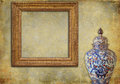 Golden frame and ancient oriental vase on a grunge background carved vintage chinese old wallpaper Stock Images
