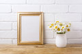 Golden frame mockup with chamomile bouquet in rustic vase