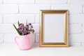 Golden  frame mockup with purple flowers in pink rustic pitcher Royalty Free Stock Photo