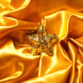 Golden glamour theme with sparkling christmas star on wavy atlas satin background close up studio shot Stock Image