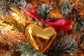 Golden hearted christmas tree ornament with red bow in an illuminated Stock Images
