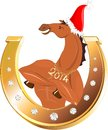 Golden horseshoe and horse athletic in christmas hat Royalty Free Stock Photography