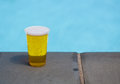 Golden lager or beer in disposable plastic cup ale a glass for party by swimming pool Stock Photo