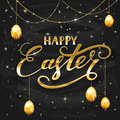 Golden lettering Happy Easter with eggs on black chalkboard back