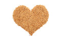 Golden linseed in a heart shape isolated on white background Royalty Free Stock Photos